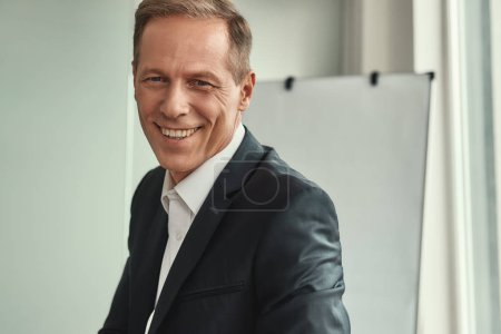 Photo for Successful businessman. Handsome and cheerful mature man in formal wear looking at camera and smiling while sitting in the office. Business people - Royalty Free Image