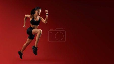Photo pour Plus haut et plus haut. Pleine longueur de jeune athlète femme en vêtements de sport sautant sur fond rouge. Concept sportif. Motivation. Mode de vie sain - image libre de droit