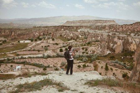 Photo pour Touriste féminine, voyageuse utilisant un smartphone, admirant une vue splendide sur un paysage pittoresque en Cappadoce, Turquie. Voyager, vacances, concept de blogueur de voyage. Plan horizontal - image libre de droit