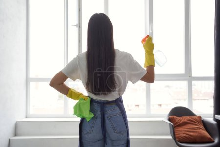 Photo for Washing windows professionally. Back view of a young woman, cleaning lady in yellow rubber gloves holding rag and spray while cleaning big window at home. Housekeeping and cleaning service concept - Royalty Free Image