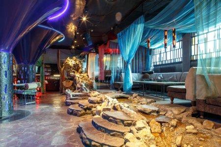 Photo pour Restaurant marocain intérieur avec sièges lounge, tables, rideaux, lumières et fontaine rivière à l'intérieur. - image libre de droit