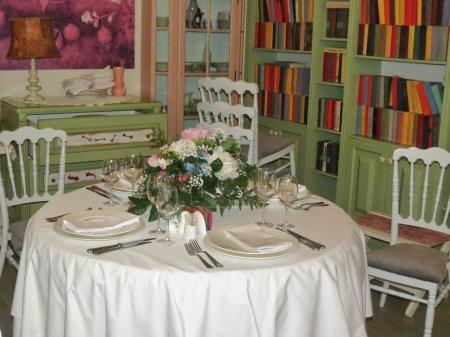 Das Innere des Restaurants ist ein elegant dekorierter Tisch mit einem schönen Blumengesteck auf dem Tisch. eine geräumige Halle mit Bibliothek und Vintage-Möbeln. stilvolles Dekor des Restaurants