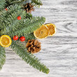 Pine branches with dried orange slices and red ber...