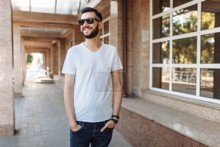 Portrait of a beautiful stylish guy, wearing glasses, on the background of a glass building,