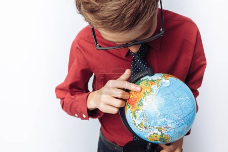 Portrait of positive and emotional schoolboy, with globe, white background, glasses, red shirt, business theme,