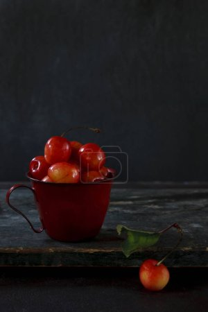 Close up photo of red fresh cherry berries on tabl...