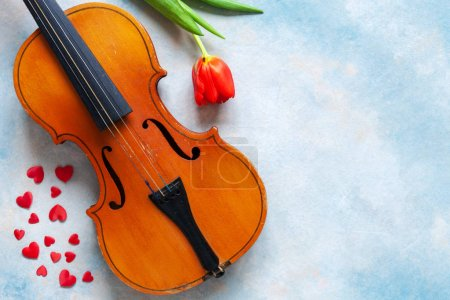 Photo pour Ancien violon, figurines de coeur rouge et tulipe rouge. Saint-Valentin, concept du 8 mars. Vue de dessus, gros plan sur fond de béton de ciel bleu - image libre de droit