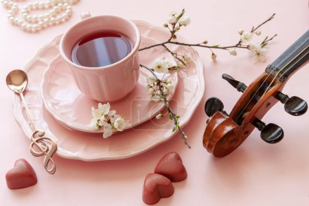 Photo for Close up of Branch of blossoming cherry cup of tea, pearl necklace, gingerbread  and violin on pastel candy pink background - Royalty Free Image