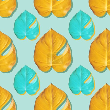 Tropical yellow and turquoise monstera leafes on turquoise background. Seamless color pattern