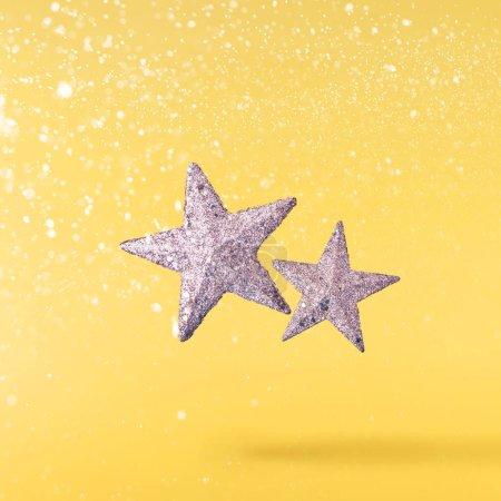Photo pour Concept de Noël. Conception de Noël créative faite en tombant dans l'air étoiles d'argent sur fond jaune. Concept minimal - image libre de droit