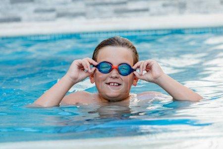Photo pour Belle enfant blonde dans la piscine en été - image libre de droit