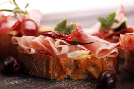 Photo for Sandwich with prosciutto or salami or crudo. Antipasti gourmet bruschetta snack - Royalty Free Image