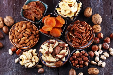 Photo for Dried fruits and assorted nuts composition on rustic table. - Royalty Free Image