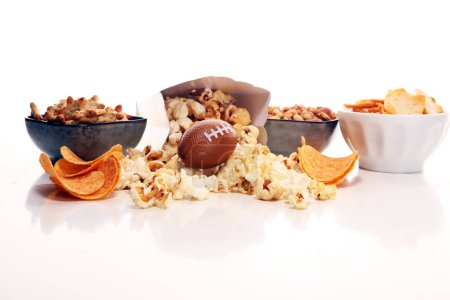 Photo for Chips, salty snacks, football on a table. Great for Bowl Game. - Royalty Free Image