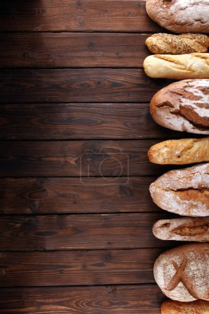 Photo for Assortment of baked bread and bread rolls on wooden table background. Bakery poster concept - Royalty Free Image