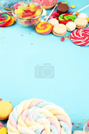 Photo for Candies with jelly and sugar. colorful array of different childs sweets and treats on blue background - Royalty Free Image