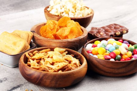 Photo for Salty snacks. Pretzels, chips, crackers in wooden bowls. Unhealthy products. food bad for figure, skin, heart and teeth. Assortment of fast carbohydrates food. - Royalty Free Image