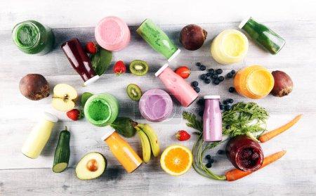 Photo pour Smoothies multicolores et jus de légumes, légumes verts, fruits et baies, fond alimentaire sain. Désintoxication et régime, alimentation propre, mode de vie sain concept - image libre de droit