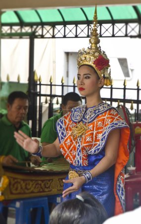Photo for BANGKOK, THAILAND - APRIL 8: a woman prays in front of dancers at the Erawan Shrine on April 8, 2016 in Bangkok, Thailand. Bangkok is the capital of, and largest city in, Thailand. - Royalty Free Image