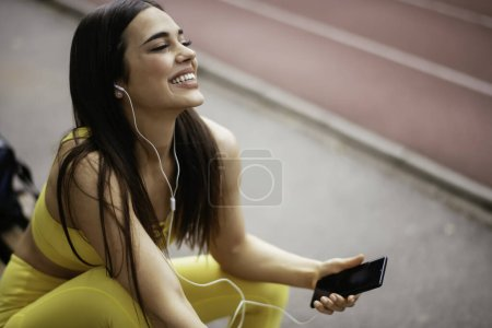 Photo for Happy woman in sportive clothes at running track listening music from smartphone with earphones - Royalty Free Image