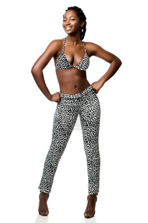 Full length portrait of attractive african woman wearing leopard pants and bikini top standing with hand on hips.Smiling girl with braided hairstyle isolated on white background.