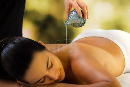 Photo pour Gros femme relaxante dans le spa de lumière faible. Thérapeute, verser l'huile de massage dos. - image libre de droit