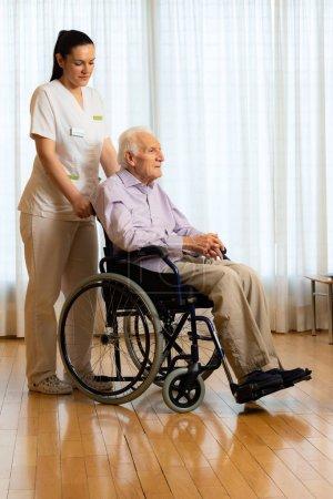 Photo pour Portrait complet d'un vieil homme handicapé assis en fauteuil roulant. Jeune infirmière debout à côté de la patiente âgée dans le salon . - image libre de droit