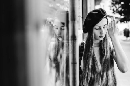 a dreamed girl in a black cap fixes her long hair with her hand on a black and white photo
