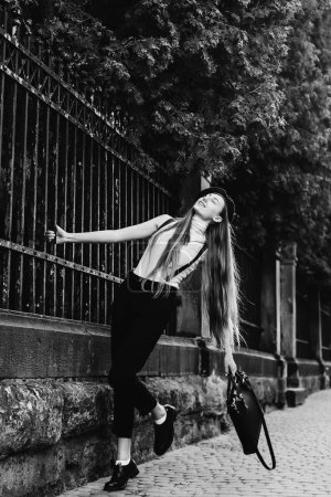 a dreamed girl holds her hand behind the fence by lifting one leg on a black and white photo