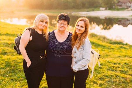 grand-mère, mère et fille embrassé et regardant dans l'objectif de la caméra sur le fond de coucher de soleil et le lac. trois générations en une seule photo