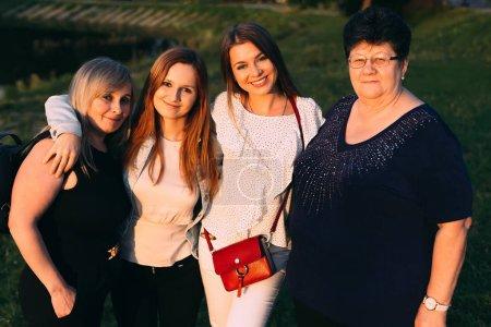 trois générations différentes de femmes qui regardent dans l'objectif de la caméra et sourire mignon. jeunes, matures et vieilles femmes sur une photo