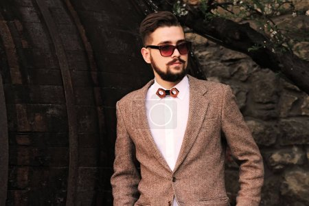 Photo for Stylish and brutal young man in a jacket with a beard and a tie looks out to the side - Royalty Free Image
