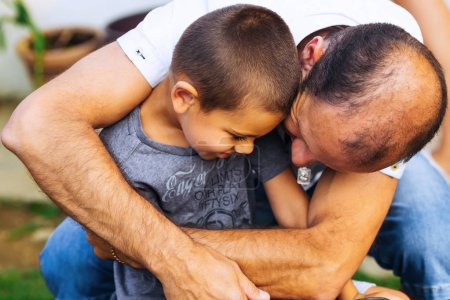 Photo pour Oncle embrasse doucement son petit neveu qui n'a pas vu depuis longtemps - image libre de droit