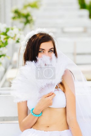 Photo for Bride with bridal veil closed the lower part of the folding fan. hen party - Royalty Free Image