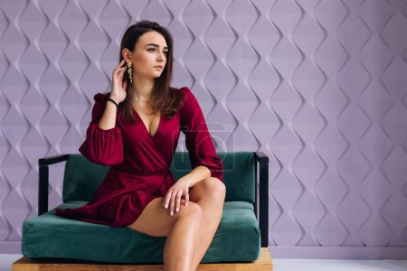 Photo for Girl posing in studio. brunette in a beautiful dress sitting on armchair. - Royalty Free Image