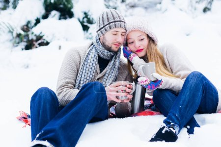 Photo for Guy and girl leaned to each other sitting in the snow and holding cups in their hands. the guy closed his eyes and the girl looks at the cup in her hand - Royalty Free Image