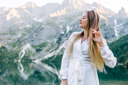 Photo for Profile of young woman with closed eyes on background of mountains and lake. white dress. - Royalty Free Image