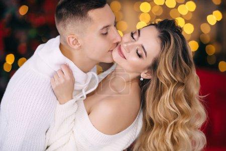 Photo pour Mec embrasse une fille aux cheveux bouclés et ils ferment les yeux. de près. fond flou . - image libre de droit