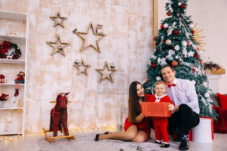 Photo for Parents sitting near Christmas tree. baby in santa costume look at camera. cozy room with toys. - Royalty Free Image