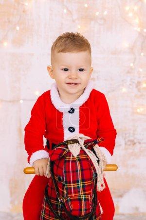 Photo pour Bébé garçon avec costume de Noël sur cheval à bascule sur le mur de fond avec des guirlandes. gros plan. - image libre de droit