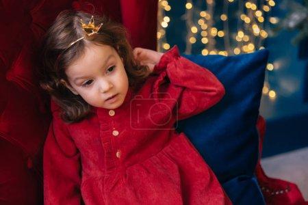 Photo pour Gros plan d'une fille en robe rouge sur un fauteuil rouge sur le fond de guirlandes. - image libre de droit