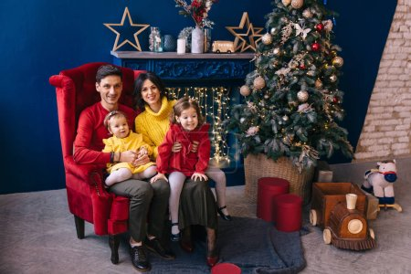 Photo for Dad and mom sitting on armchair by the fireplace and Christmas tree and little daughters sit with them. look at camera. - Royalty Free Image