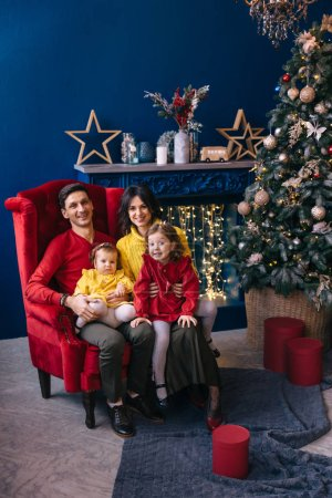 Photo for Parents and little daughters sitting on armchair by the fireplace and Christmas tree. smile and look at camera. - Royalty Free Image