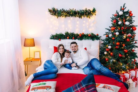 Photo for Parents in bedroom on bed kissing and between them little son. beautiful Christmas tree and decorations by the bed. - Royalty Free Image