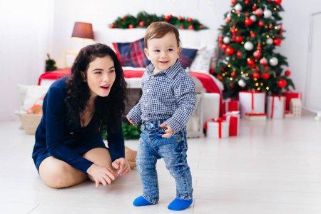 Photo pour Maman s'assoit par terre dans la chambre et joue avec un petit garçon. chambre avec sapin de Noël et cadeaux. - image libre de droit