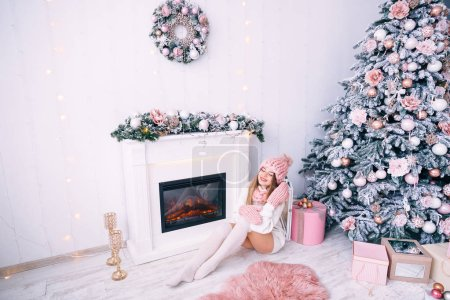 Photo for Girl in warm knitted winter clothes sits by the fireplace and Christmas tree with gifts. cozy room. - Royalty Free Image