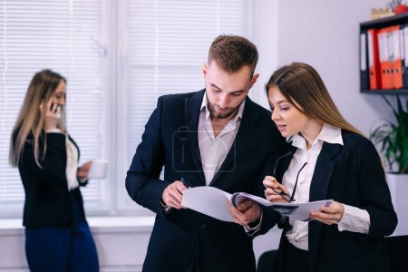 Photo pour Homme d'affaires et femme d'affaires discutent du travail pendant que leur collègue parle au téléphone en arrière-plan - image libre de droit