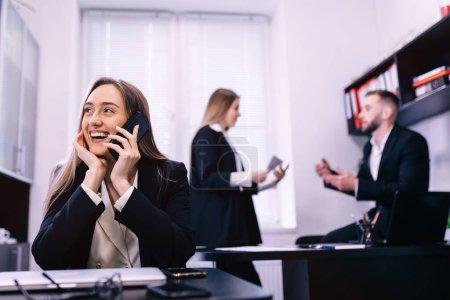Photo pour Femme au téléphone sourit dans le bureau moderne occupé. Chers collègues, discutant des travaux en arrière-plan - image libre de droit