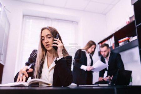 Photo pour Communication d'entreprise. Femme d'affaires Parler sur téléphone portable et prendre des notes dans le bureau moderne tandis que ses collègues communiquent sur fond - image libre de droit