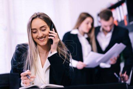 Photo pour Femme d'affaires heureuse appelant sur un téléphone portable et prenant des notes sur un bureau au bureau - image libre de droit